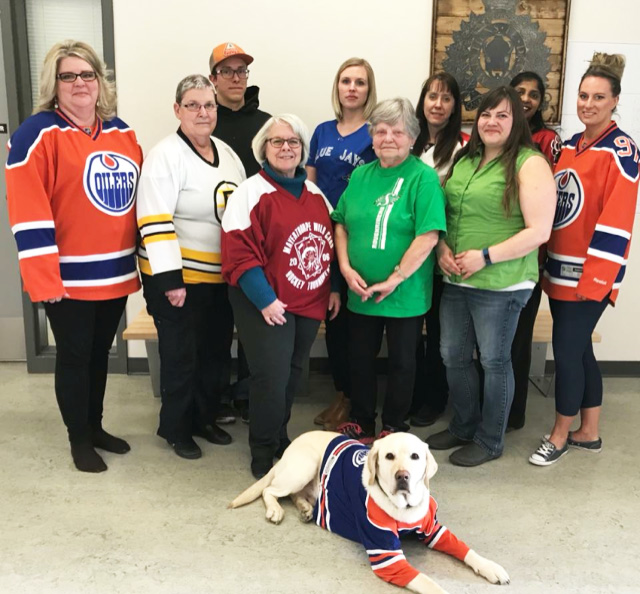 The Bonnyville Victim Services staff posing sport jerseys, Odie the support dog in front with a jersey on.