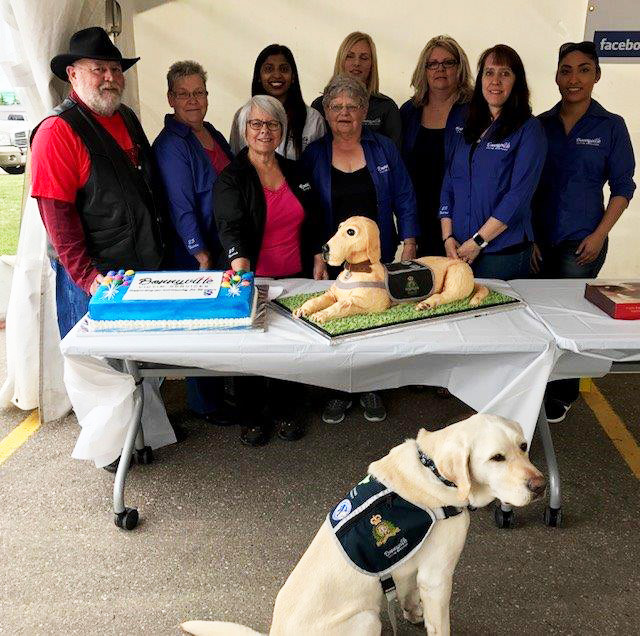 The Bonnyville Victim Services staff posed together with a large blue cake and a cake shaped like Odie, the support dog.