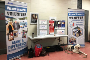 Bonnyville Victim Services table set up at an event with two large standing-banners on either side, Odie laying in front