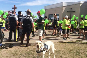 Odie the support dog standing in front of a large goup of people and police officers, green balloons scattered everywhere